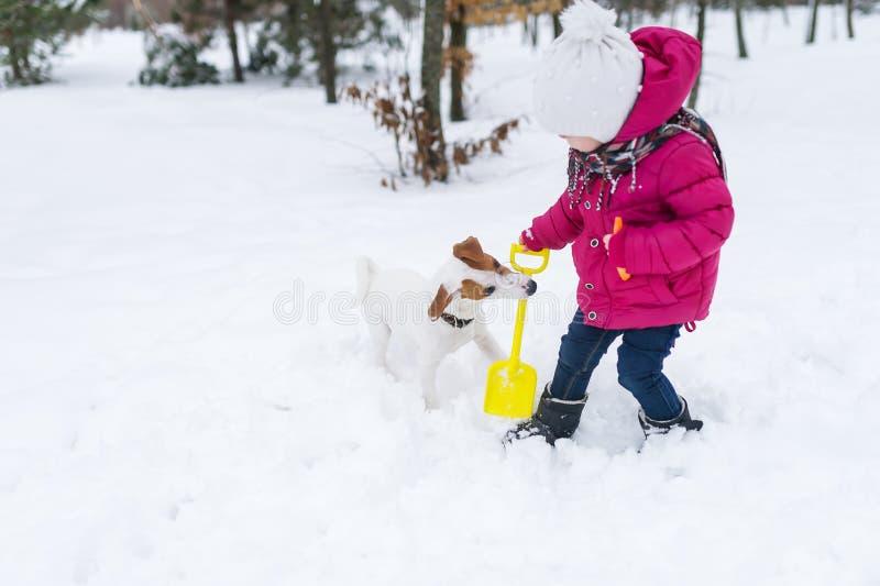 Bebé con el juego del perro en parque del invierno fotos de archivo