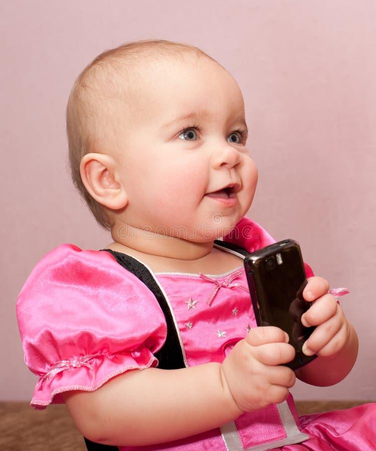 Bebé con el móvil fotos de archivo