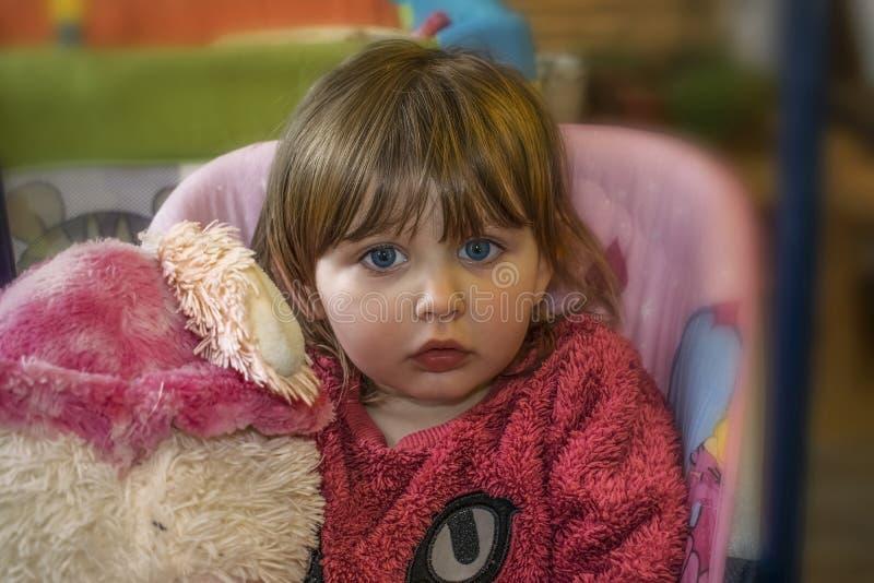 Bebé con el pelo rubio que se sienta en el oscilación foto de archivo