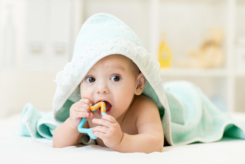 Bebé con el teether en boca bajo baño de la toalla en el cuarto de niños imagenes de archivo