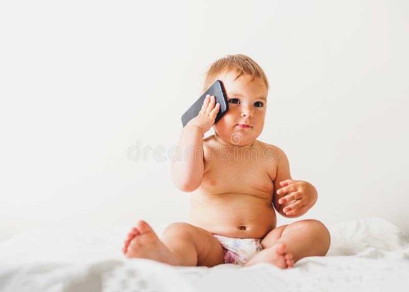Bebé con el teléfono móvil cerca de su oído, llamando alguien, espacio de la copia, desarrollo de la GEN z foto de archivo