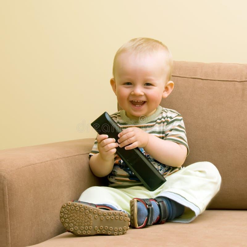 Bebé con el telecontrol de la TV fotos de archivo libres de regalías