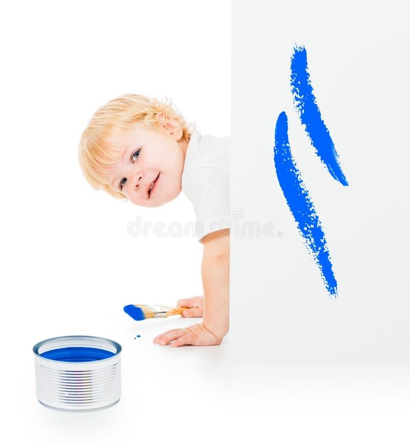 Bebé con la brocha en todos los fours detrás de la pared pintada imagenes de archivo