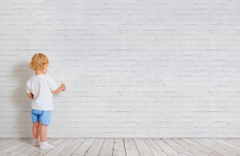 Bebé con la brocha que retrocede cerca de la pared de ladrillo imagenes de archivo