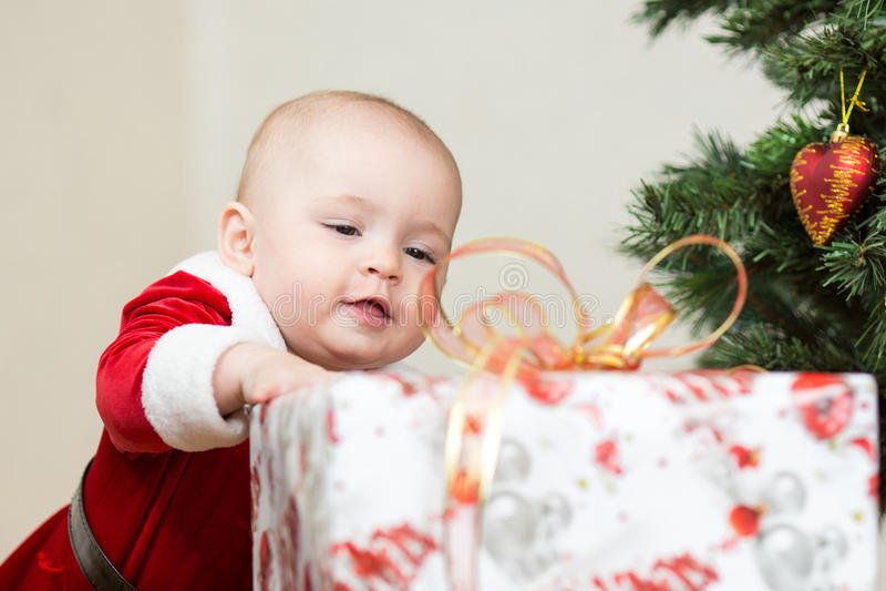 Bebé con la caja de regalo grande en el árbol de navidad imagen de archivo