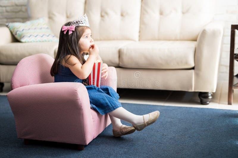 Bebé con la corona de la princesa que ve la TV en casa fotografía de archivo libre de regalías