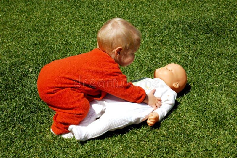 Bebé con la muñeca imagenes de archivo