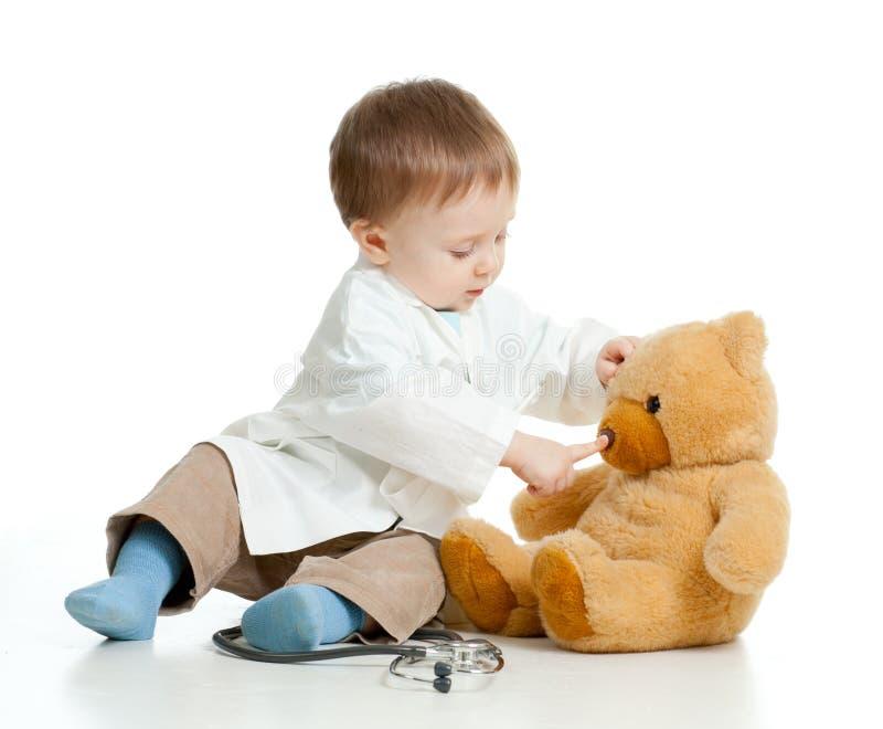 Bebé con la ropa del doctor y del oso de peluche imagenes de archivo