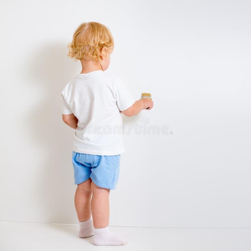 Bebé con la vista posterior de la brocha que se coloca cerca de la pared en blanco imágenes de archivo libres de regalías