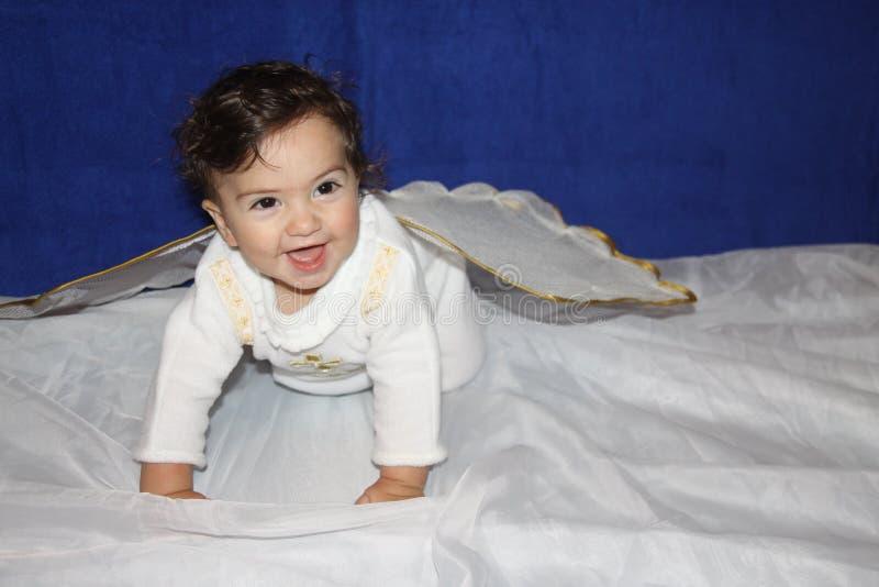 bebé con las alas del ángel que comienzan a caminar vestido en un traje para el bautismo imagen de archivo