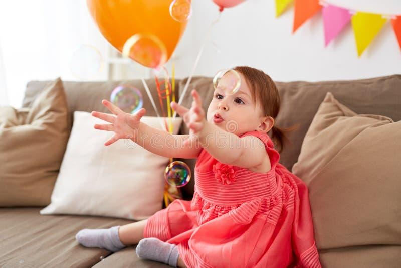 Bebé con las burbujas de jabón en fiesta de cumpleaños imágenes de archivo libres de regalías