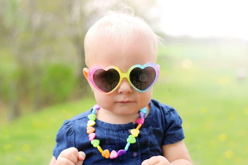 Bebé con las gafas de sol en forma de corazón afuera imagenes de archivo