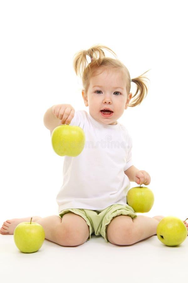Bebé con las manzanas verdes fotografía de archivo