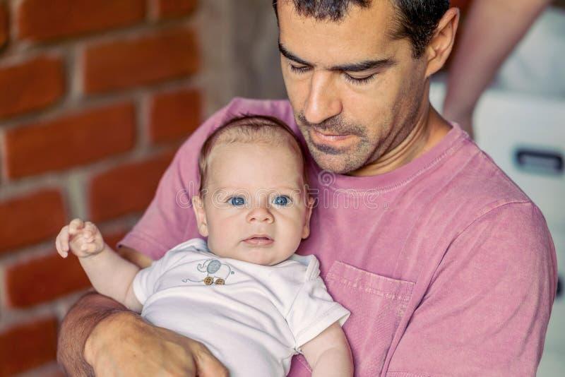 Bebé con los ojos azules potentes en el padre Arms fotografía de archivo