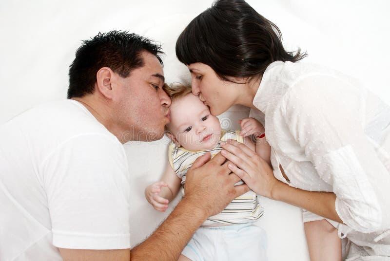 Bebé con los padres que mienten en una cama fotografía de archivo libre de regalías