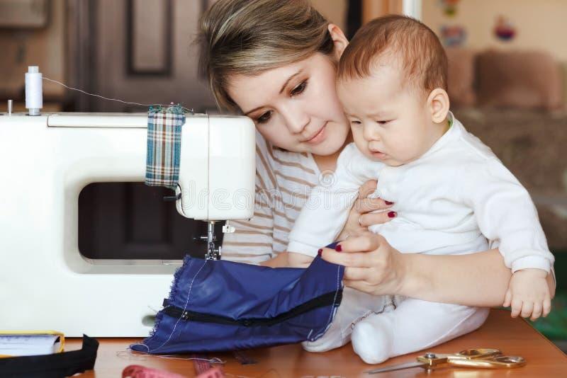 Bebé con su costurera de la madre, hogar, luz natural, niño curiosamente que mira a la máquina de coser Cuidado de niños y trabaj imagenes de archivo