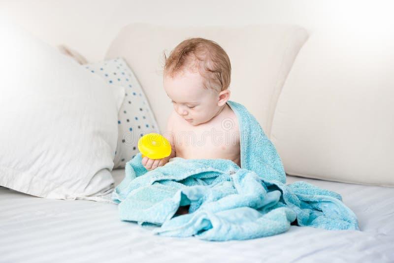 Bebé cubierto en la toalla azul que juega con el pato de goma amarillo o fotos de archivo