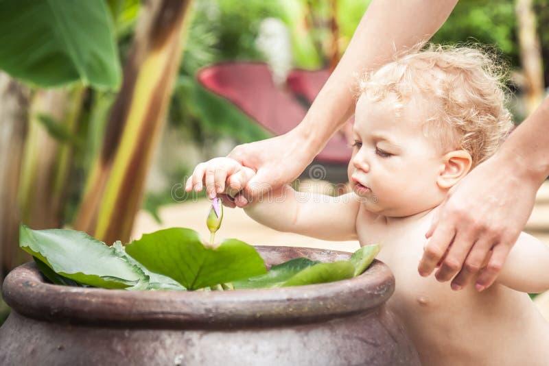 Bebé curioso con la flora de exploración de la madre en jardín tropical durante vacaciones de verano imagen de archivo