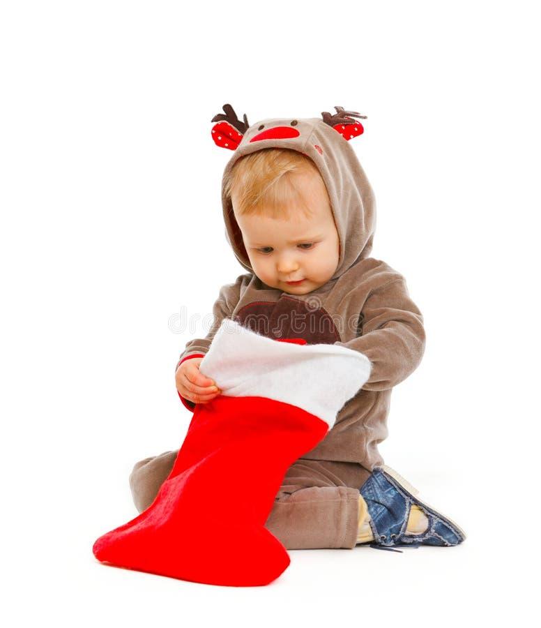 Bebé curioso que controla el calcetín de la Navidad imagen de archivo libre de regalías