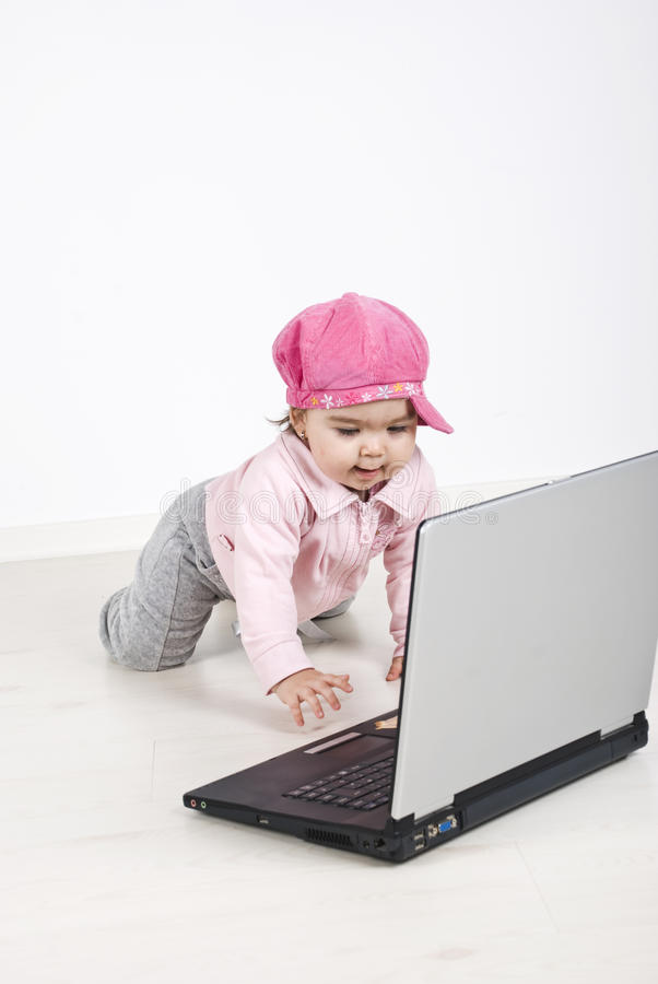Bebé curioso que se arrastra a la computadora portátil imagenes de archivo