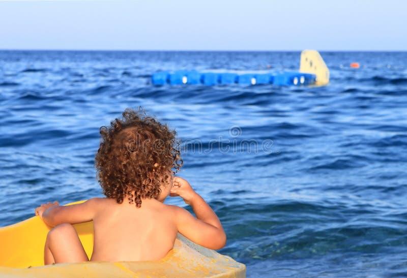 Bebé Curly em uma canoa que presta atenção ao mar   fotografia de stock royalty free