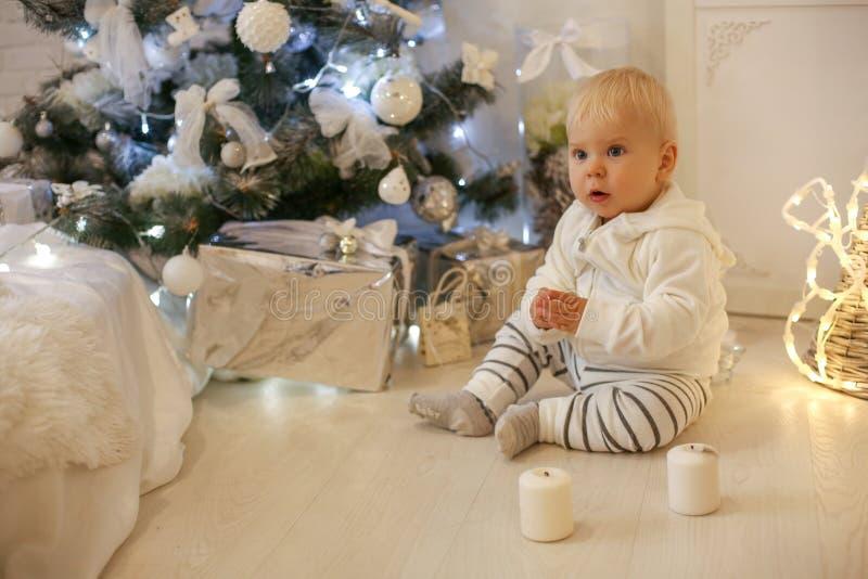 Bebé de 1 año lindo en la ropa acogedora, presentando en el Año Nuevo diciembre imagenes de archivo