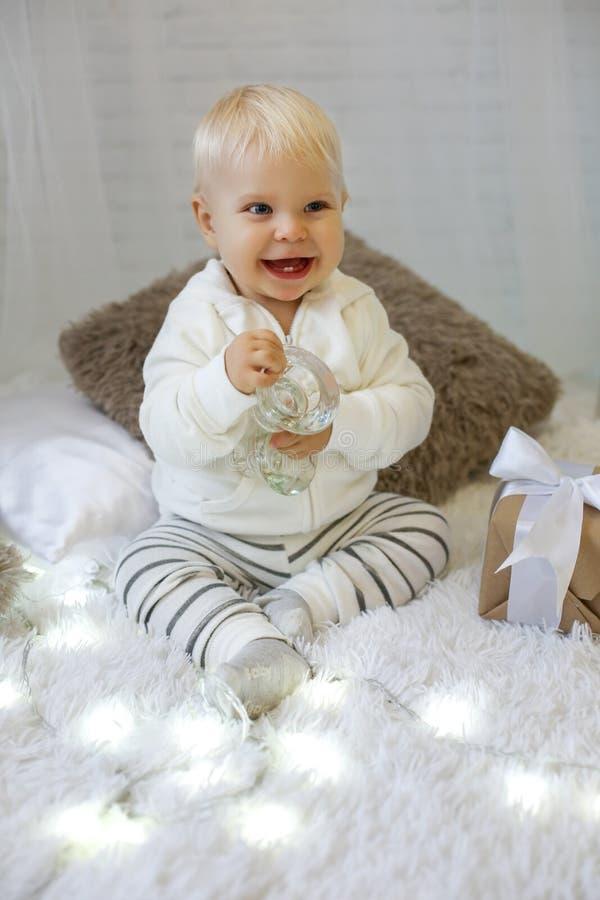 Bebé de 1 año lindo en la ropa acogedora, presentando en el Año Nuevo diciembre imagen de archivo libre de regalías