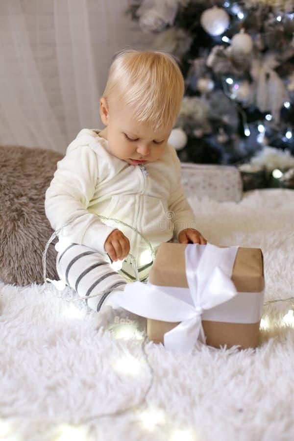 Bebé de 1 año lindo en la ropa acogedora, presentando en el Año Nuevo diciembre fotografía de archivo
