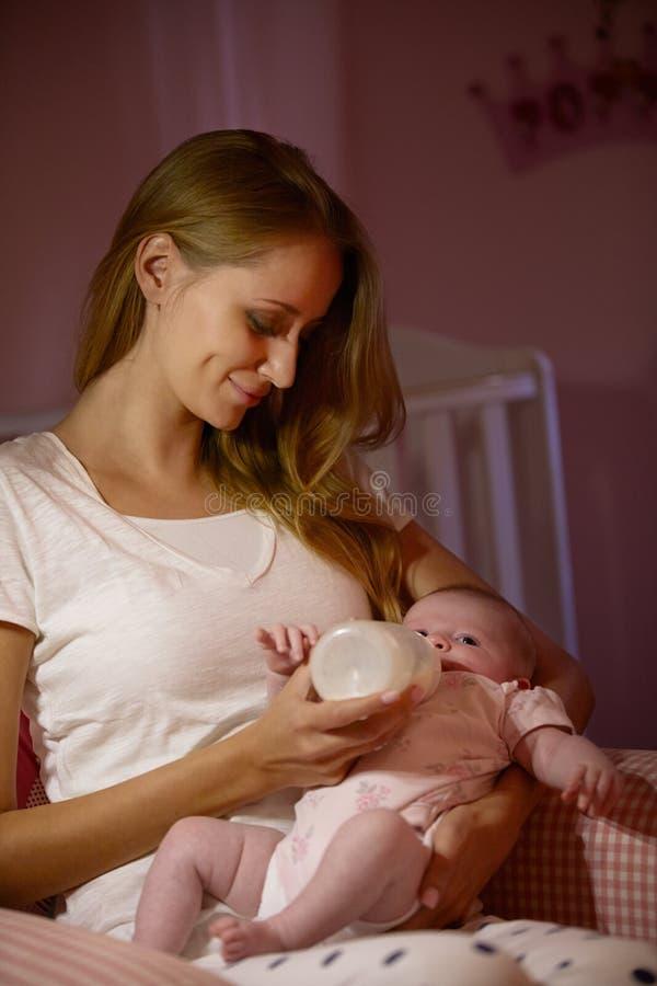 Bebé de alimentación de la madre con la botella en cuarto de niños fotografía de archivo