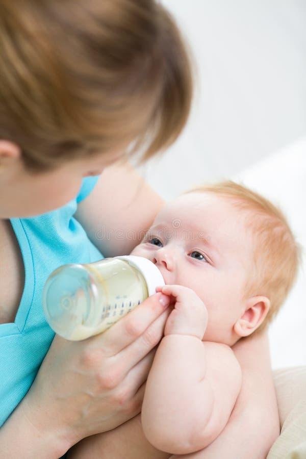 Bebé de alimentación de la madre de la botella imagen de archivo libre de regalías