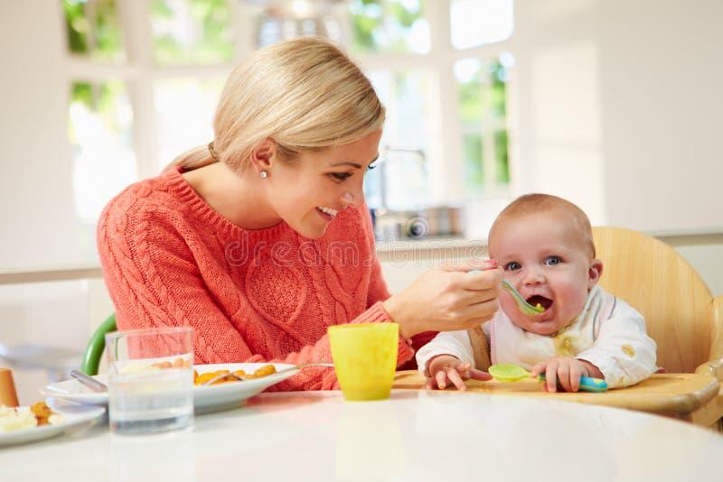 Bebé de alimentación de la madre que se sienta en trona en la hora de comer imagenes de archivo