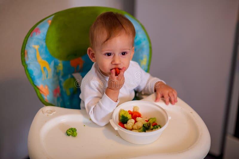 Bebé de alimentación - muchacho adorable que come verduras fotos de archivo