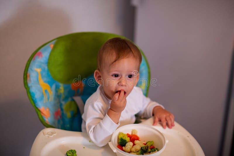 Bebé de alimentación - niño adorable que come verduras foto de archivo libre de regalías