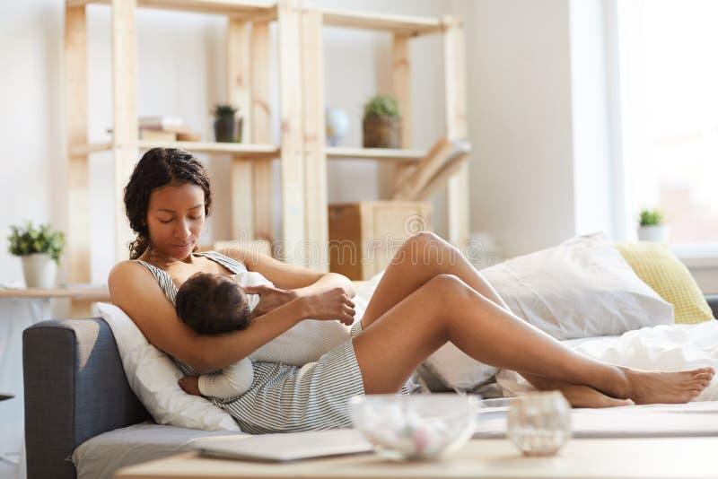 Bebé de amamantamiento de la mamá negra imagenes de archivo