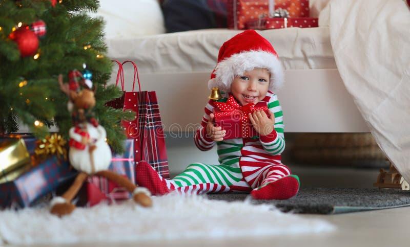 Bebé de Appy en pijamas con los regalos el mañana de la Navidad cerca foto de archivo libre de regalías