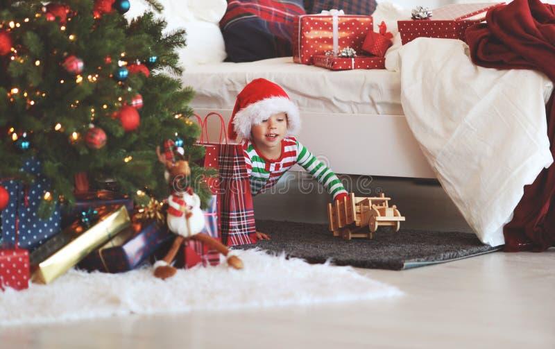 Bebé de Appy en pijamas con los regalos el mañana de la Navidad cerca imagenes de archivo
