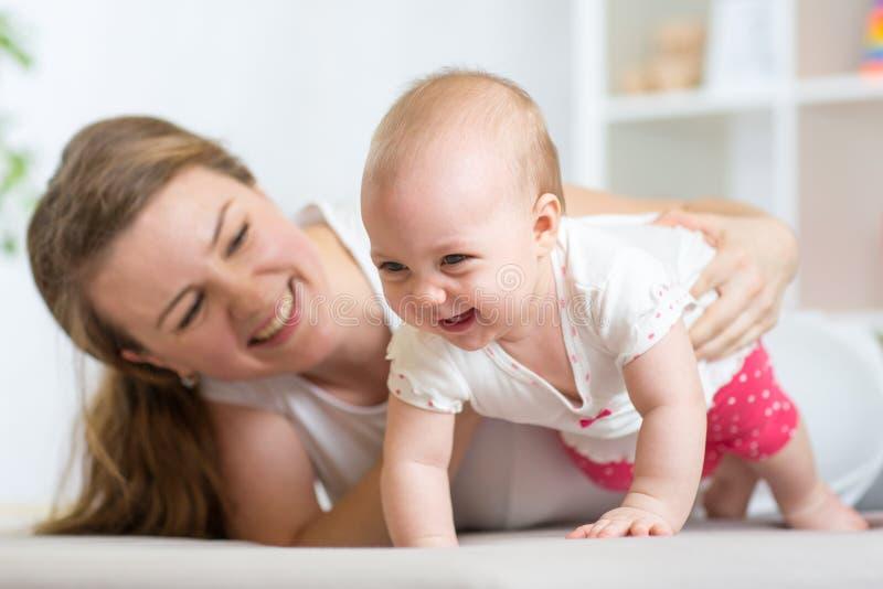 Bebé de arrastre feliz con la madre fotografía de archivo