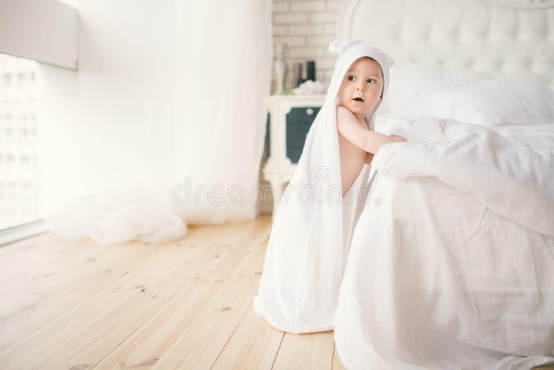 Bebé de cinco meses del bebé recién nacido en el dormitorio al lado de una cama blanca grande en el piso de madera envuelto en un imágenes de archivo libres de regalías
