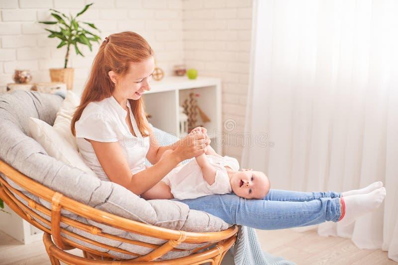 Bebé de la gimnasia mujer que hace ejercicios con el bebé para su desarrollo dé masajes a un pequeño bebé recién nacido fotos de archivo libres de regalías