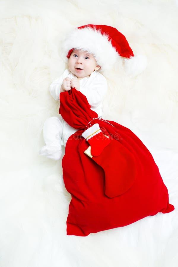 Bebé de la Navidad que desgasta el bolso rojo de la explotación agrícola del sombrero imagen de archivo