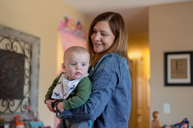Bebé de la tenencia de la mujer mientras que visita con la familia foto de archivo libre de regalías