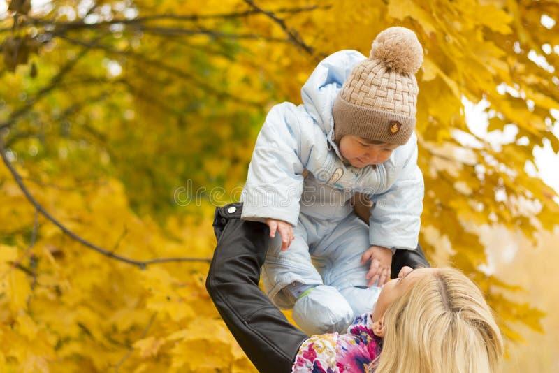 Bebé de levantamiento de la madre joven para arriba Concepto de familia feliz foto de archivo