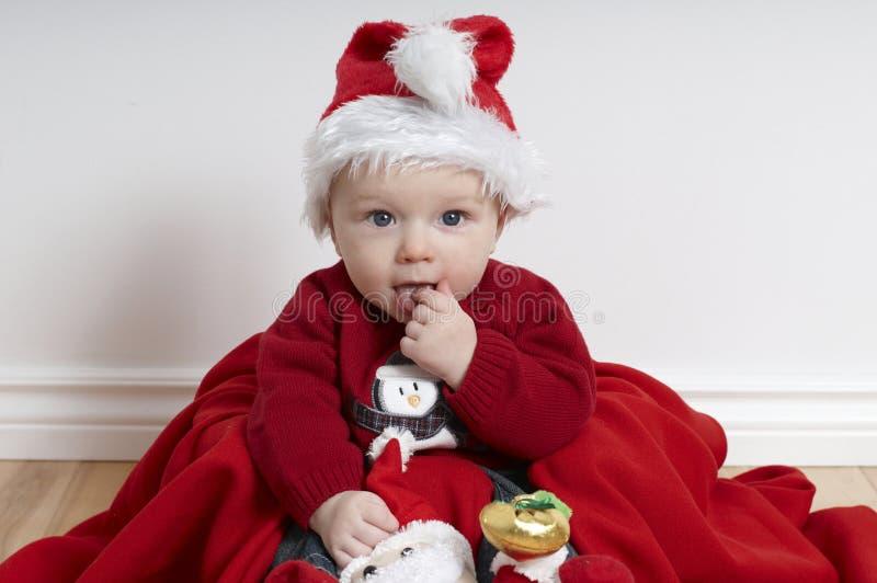 Bebé de 6 meses en la Navidad que lleva el sombrero de santa fotos de archivo