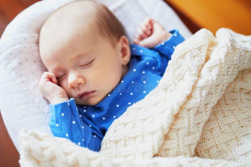 Bebé de 1 meses que duerme debajo de la manta hecha punto imagenes de archivo