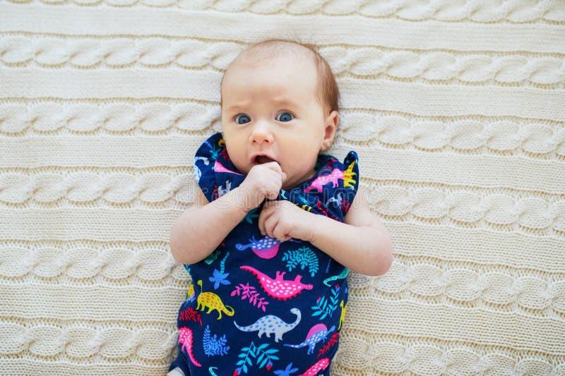 Bebé de 1 meses sorprendido que miente en la manta hecha punto fotos de archivo