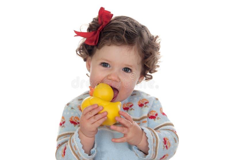 Bebé de ojos azules hermoso que aspira un pato de goma imágenes de archivo libres de regalías