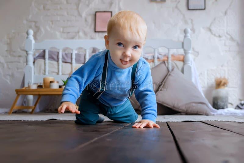 Bebé de ojos azules hermoso que se arrastra en el piso de madera fotos de archivo