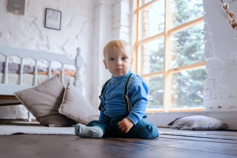 Bebé de ojos azules triste hermoso que se sienta en un piso de madera y que mira la cámara imagen de archivo libre de regalías