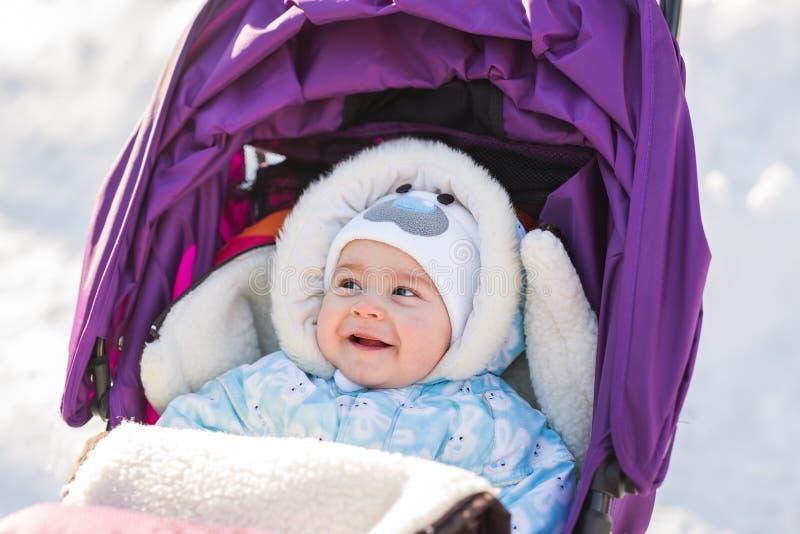 Bebé de risa divertido que se sienta en un cochecito en viejo día de invierno de c foto de archivo