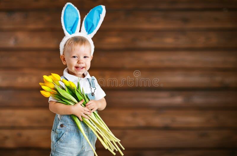 Bebé de risa feliz en oídos del conejito con los tulipanes amarillos en el wo foto de archivo